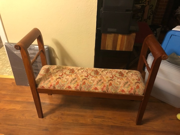 Brown wooden framed floral padded armchair