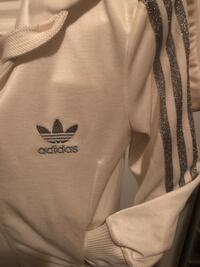 White Adidas jacket with silver trim on sleeves and zipper hood Toronto