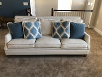 White fabric 3-seat sofa trimmed in blue with throw pillows
