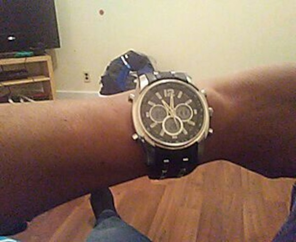 round silver chronograph watch with black leather strap