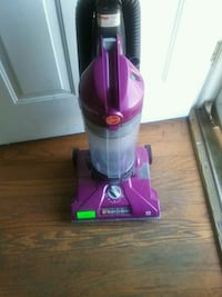 purple and black Bissell upright vacuum cleaner