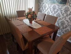 rectangular brown wooden table with six wooden chairs with brown pads