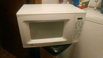 White GE microwave with paperwork