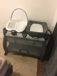 baby's black and gray Graco pack n play