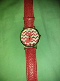 round black analog watch with red leather strap