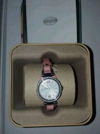 round silver analog watch with pink leather strap