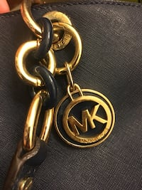 gold and black Michael Kors pendant necklace