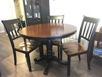 round brown wooden table with four chairs dining set Coquitlam, V3E