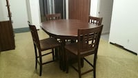 oval brown wooden dining table with four wooden chairs set