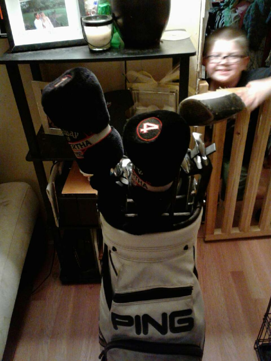 black metal golf club set with white Ping golf bag