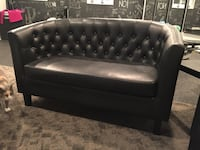 Black leather curved loveseat