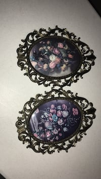 two oval flower arrangement paintings and ornate frames