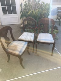 Three sturdy antique chairs with blue and white cushions ,no arms