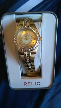 round gold analog watch with link bracelet in box