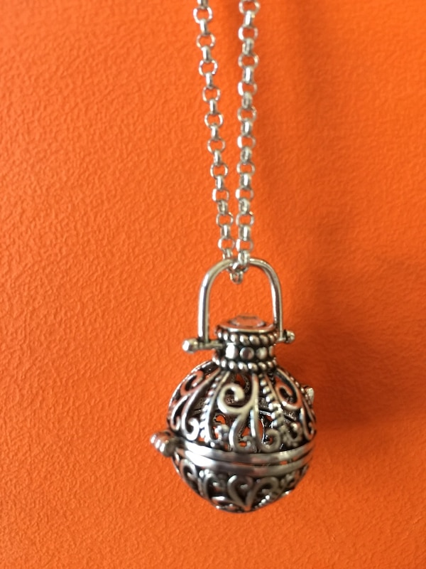Silver locket with silver chain. Great for keepsakes or pearls