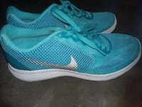 pair of teal-and-white Nike running shoes