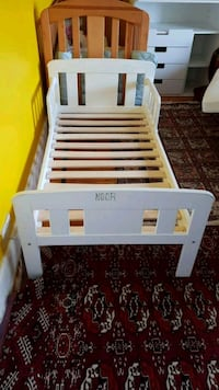 white wooden bed frame with white mattress
