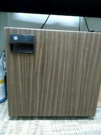 Small faux wood front refrigerator. Dorm room or small  office size.