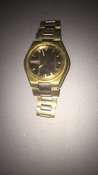 round gold analog watch with gold link bracelet Spartanburg