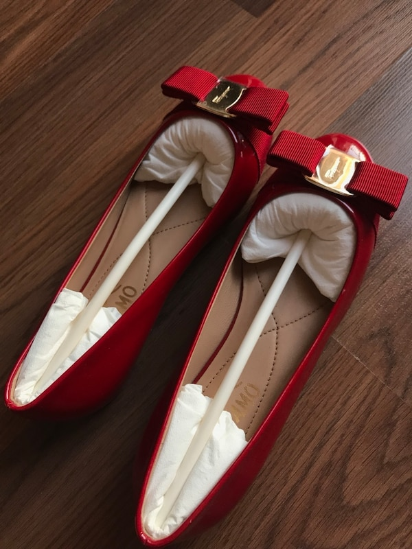 pair of women's red patent leather flats with bow accent