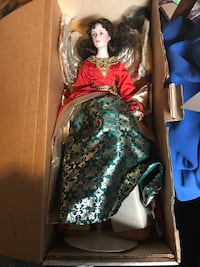 porcelain doll wearing red and teal long-sleeve dress with box