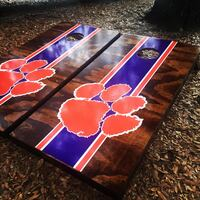 two red and brown wooden corn hole table