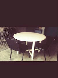 round white wooden table with four chairs