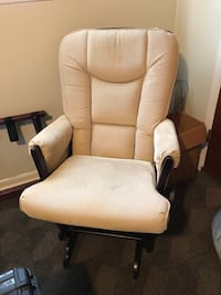 Tan padded brown wooden glider chair