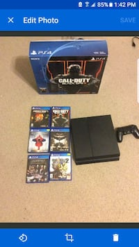 black Sony PS4 console with controller and game ca