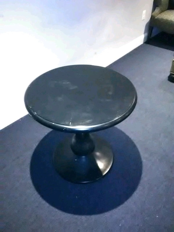 All black round hard wood table  377a9cfd-0176-415d-bc34-f7145c83bed5