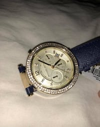 Round gold chronograph watch with navy leather strap