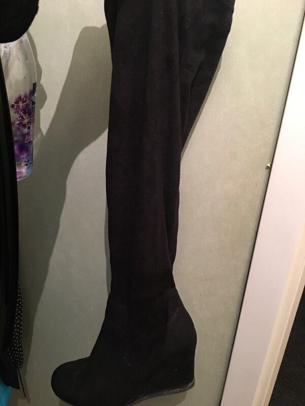 unpaired black suede knee-high boot