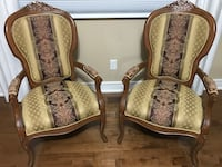 brown wooden framed beige padded armchairs