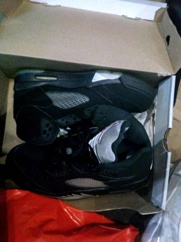 pair of black Air Jordan 5's in box