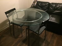Round glass top table with two chairs
