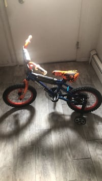 toddler's black and red bicycle with training wheels null