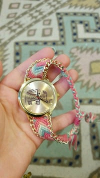 round gold analog watch with pink leather strap