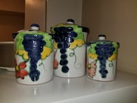 three white-green-and-purple ceramic canisters