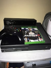 black Xbox One console with controller and game