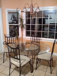 round clear glass-top dining table with brown steel base MACON