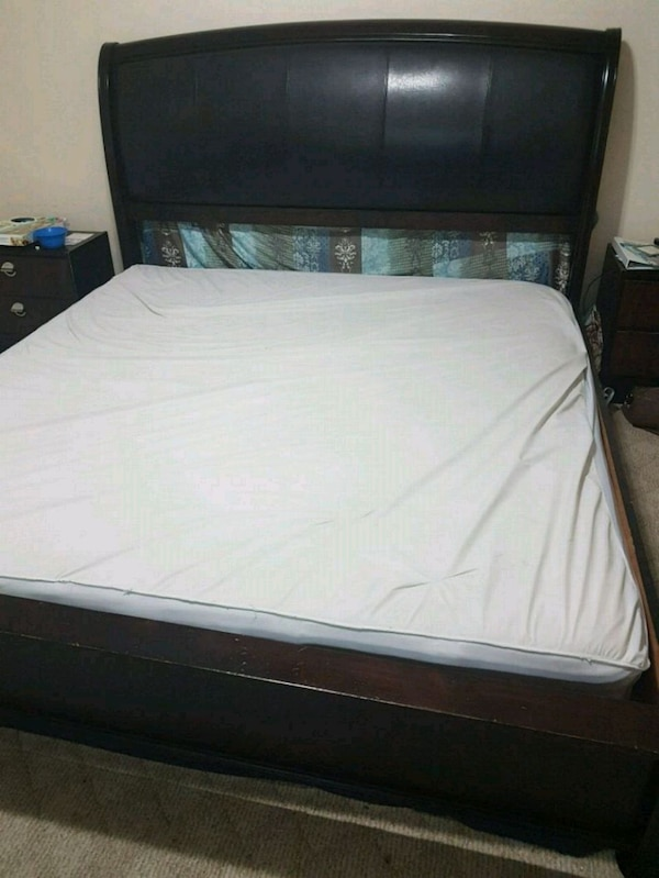 white mattress and black wooden king size bed dfaf8291-4b66-403b-9c49-47c6f1a84be3