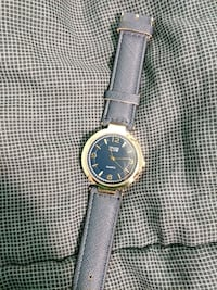 round gold-colored analog watch with black leather strap Lyn, K0E 1M0