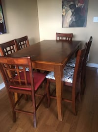 Brown wood table. With 8 chairs.  Shown with leaf out. With leaf table is a square Burlington, L7T 1G1