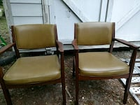 two brown leather armchairs with brown wooden frames