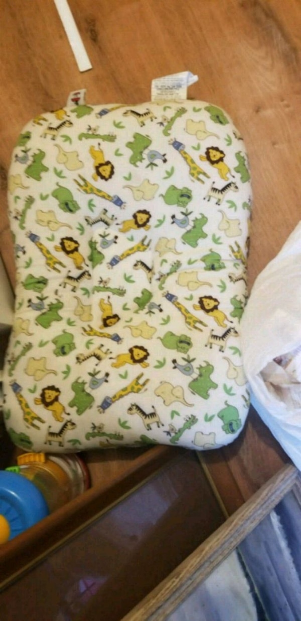 white and green animal print nursing pillow