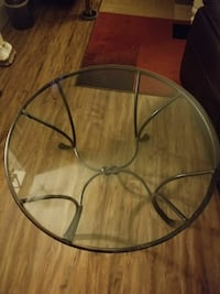 round clear glass top table with black metal base