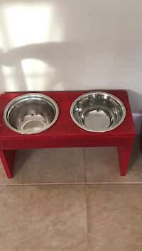 Dog food stands with stainless steel bowls.