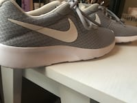 Pair of gray and white nike running shoes
