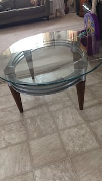 round clear glass top table with black wooden base