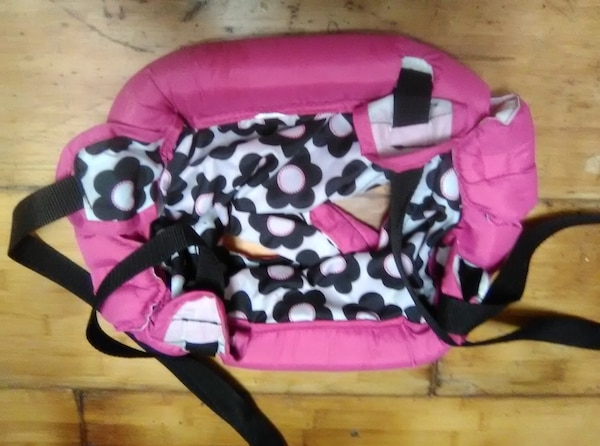 baby's pink and black polka dot carrier